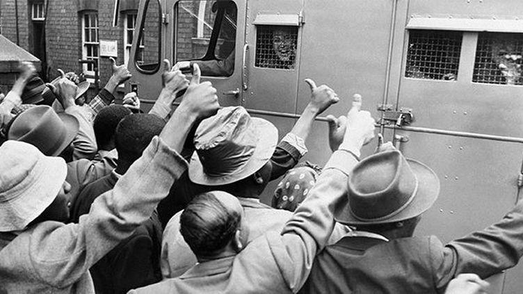 Des sympathisants de l'ANC saluent le passage d'un fourgon cellulaire transportant des militants anti-apartheid, le 28 décembre 1956. (AFP)