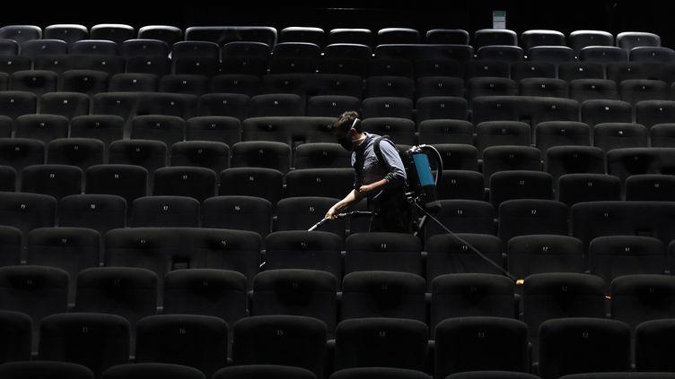 Un employé nettoie la salle d'un cinéma du groupeCGR à Cagnes-sur-Mer le 22 juin 2020. Photo d'illustration. (SEBASTIEN NOGIER / EPA)