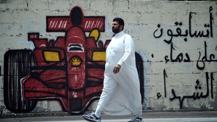 """Un Bahreïnien passe devant un tag demandant : """"Allez vous courir sur le sang des martyrs ?"""", le 9 avril 2012, à Barbar (Bahreïn). (STR / AFP)"""