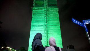 La tour Grenfell, à Londres, éclairée en vert, à minuit, le 14 juin 2018, pour commémorer l'incendie qui la ravagea un an plus tôt. (TOLGA AKMEN / AFP)