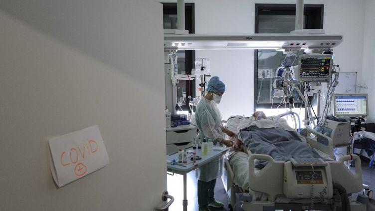 Une soignante s'occupe d'un patient malade du Covid-19 à l'hôpital Pasteur à Colmar (Haut-Rhin), le 22 avril 2021. (SEBASTIEN BOZON / AFP)