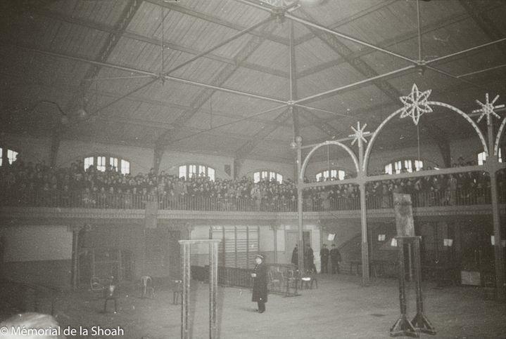 Les hommes arrêtés sont parqués dans les gradins à l'étage. Le centre du gymnase est vidé. Seuls des policiers circulent. La première étape de la rafle a déjà eu lieu: les Juifs convoqués sont entrés dans la souricière. On découvre pour la première fois l'intérieur de Japy et les centaines d'hommes juifs entassés.  (MEMORIAL DE LA SHOAH)