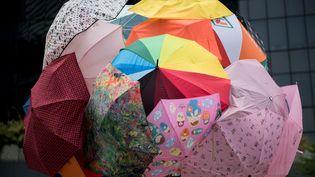 """Les parapluies servent à la fois à protéger les manifestants des gaz lacrymogènes, comme dimanche, et de la pluie. A tel point que le mouvement est baptisé """"révolution des parapluies"""". (ALEX OGLE / AFP)"""