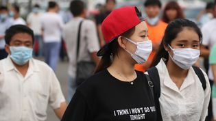 Des habitants de la ville de Tianjin(Chine) portent un masque pour se protéger de la pollution, vendredi 14 août, après de graves explosions sur un site qui stockait des produits chimiques dangereux, deux jours plus tôt. ( AFP )