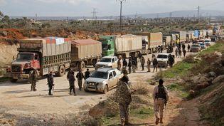 Des combattants rebelles observent l'arrivée d'un convoi des Nations unies à Kafraya (Syrie), le 14 mars 2017. (OMAR HAJ KADOUR / AFP)