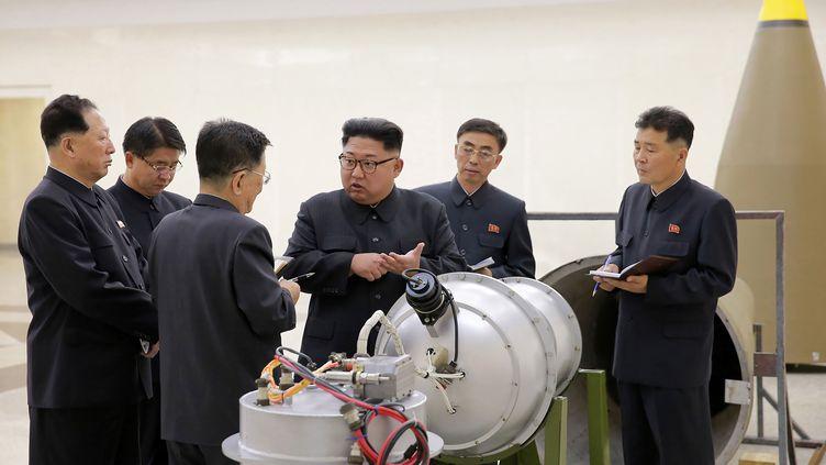Le leader nord-coréen, Kim Jong-un, devant la charge d'un missile démonté, sur un cliché diffusé le 3 septembre 2017. (KCNA VIA KNS / AFP)