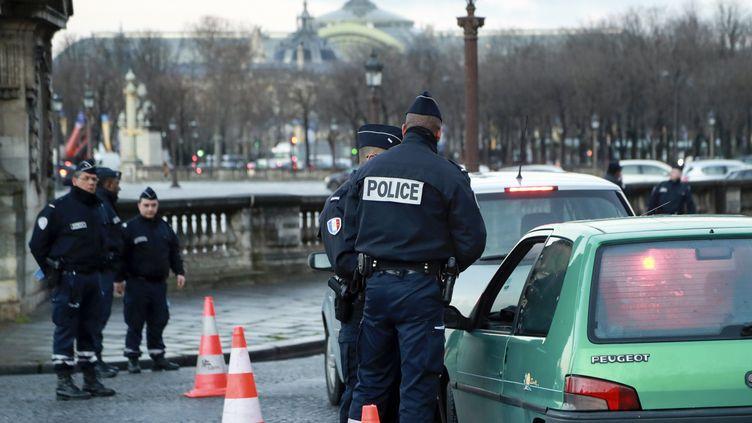 """Des agents de police contrôlent un véhicule place de la Concorde à Paris, le 10 janvier 2017, pour vérifier la présence d'une vignette """"Crit'Air"""". (JACQUES DEMARTHON / AFP)"""
