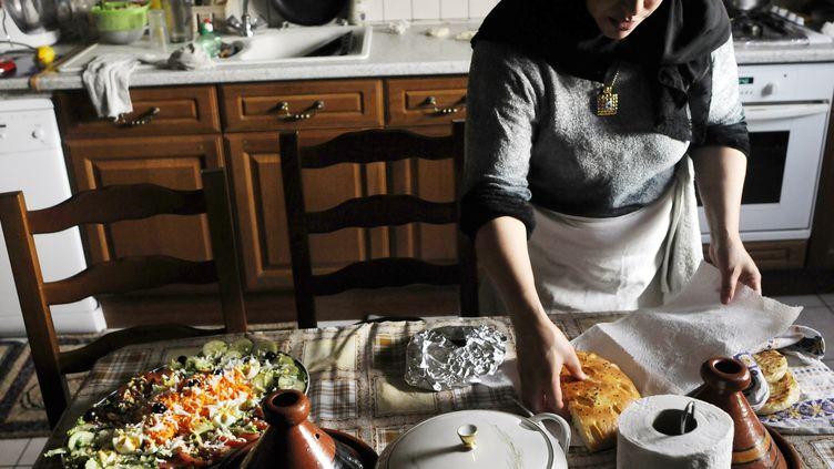 Une femme musulmane prépare le repas de rupture du jeûne pendant le ramadan, à Mulhouse (Haut-Rhin), en septembre 2009. (SEBASTIEN BOZON / AFP)