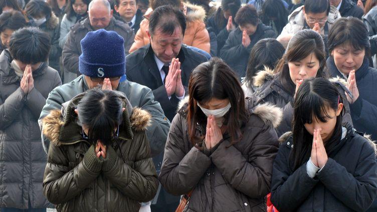 Dans les villes et villages japonais dévastés, les proches des quelque 19.000 morts et disparus se sont recueillis dans le chagrin et la douleur, au cours de cérémonies improvisées sur les lieux de la tragédie. (KAZUHIRO NOGI / AFP)