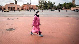 Une Marocaine sur la place Jamaa el-Fna désertée en raison de l'appel des autorités à ne plus se déplacer sans raison impérative, le 18 mars 2020. (FADEL SENNA / AFP)