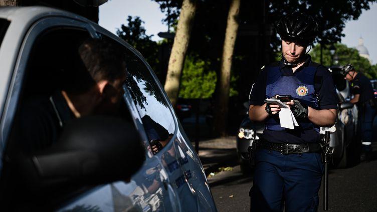 Un agent de la surveillance de Paris verbalise un conducteur, le 1er juillet à Paris. (PHILIPPE LOPEZ / AFP)