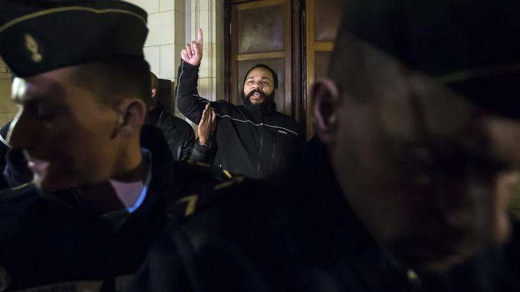 """L'humoriste Dieudonné M'Bala M'Bala mime un """"soleil"""", un geste de ralliement de ses sympathisants, le 4 février 2015, au palais de justice de Paris. (MAXPPP)"""