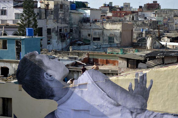 Le petit garçon cubain collé par JR regarde les toits de La Havane (11 avril 2019)  (Yamil Lage / AFP)