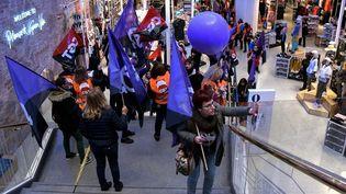 Des manifestantes, dans un magasin de vêtements de Madrid, le 8 mars 2018, appellent à la grève des femmes en Espagne. (OSCAR DEL POZO / AFP)