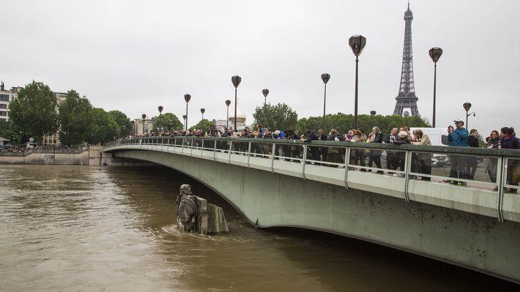 Des passants observent la crue de la Seine depuis le pont de l'Alma, à Paris, le 3 juin 2016. Le niveau de la Seine est monté à 6,10 mètres à Paris, dans la nuit du 3 au 4 juin. Un niveau qui n'avait pas été atteint depuis 34 ans. (CAROLINE PAUX / CITIZENSIDE / AFP)