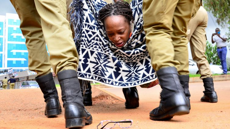 L'universitaire ougandaise Stella Nyanzi regarde ses lunettes au sol alorsque des policiers l'interpellent le 18 mai 2020 à Kampala, la capitale ougandaise,pour avoir manifesté contre la façon dont le gouvernement distribuel'aide alimentaire pendant leconfinement décrété pour contrôler la propagation du Covid-19. (ABUBAKER LUBOWA / X07299)