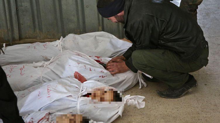 Un homme pleure près du corps d'une victime des bombardements qui visent la Ghouta orientale, près de Damas (Syrie), le 20 février 2018. (AMER ALMOHIBANY / AFP)