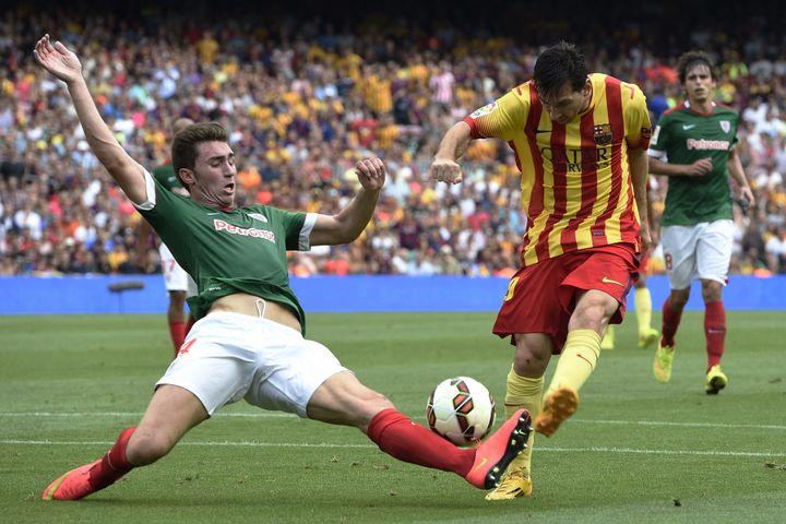 Le geste défensif d'Aymeric Laporte face à Lionel Messi lors d'une rencontre entre le FC Barcelone et l'Athletic Bilbao au Camp Nou, le 13 septembre 2014. (LLUIS GENE / AFP)