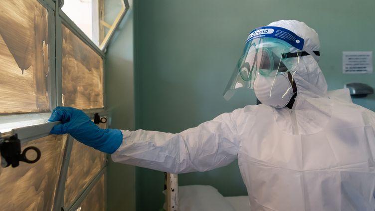 Destinée à montrer la préparation du Zimbabwe face au coronavirus, l'image d'un infirmier équipé de gants, d'un masque et d'une visière de protection à l'hôpital Wilkins à Harare, spécialisé dans les maladies infectieuses (photo du 11 mars 2020). (JEKESAI NJIKIZANA / AFP)