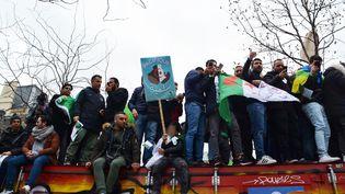 Des manifestants sur un container place de la République à Paris lors du rassemblement qui s'opposait à une cinquième candidature de Abdelaziz Bouteflika à la présidentielle d'avril 2019. Photo prise le 3 mars 2019. (JEAN-CHRISTOPHE BOURDILLAT / RADIO FRANCE)