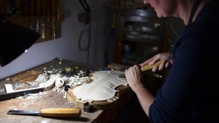 Marianne Jost, luthière suisse installée à Crémone (Italie), taille le fond d'un violon. (MIGUEL MEDINA / AFP)