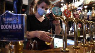 Une serveuse sert une bière dans un pub à Londres (Grande-Bretagne). Photo d'illustration. (DANIEL LEAL-OLIVAS / AFP)