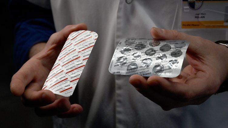 Un membre du personnel médical de l'Institut hospitalo-universitaire de Marseille montre, le 26 février 2020, des plaquettes de Nivaquine et de Plaquenil, qui contiennentchloroquine ethydroxychloroquine. (GERARD JULIEN / AFP)