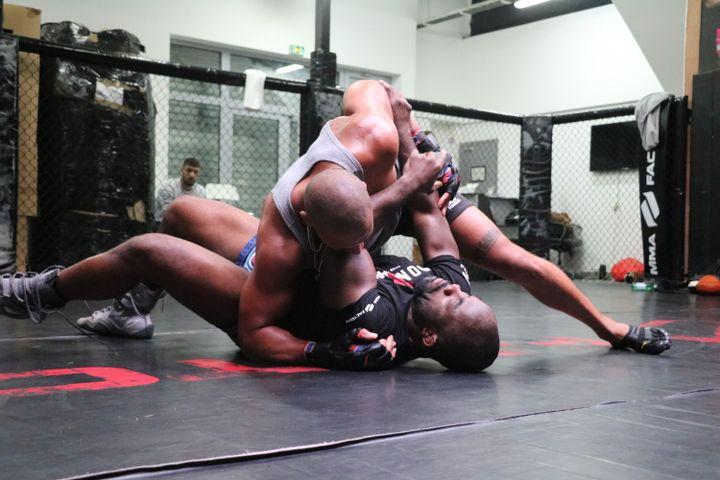 Le combattant français de MMA Ciryl Gane, au sol à l'entraînement avec son coach Fernand Lopez à la MMA Factory