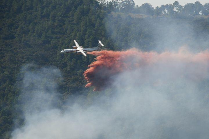 Un avion Bombardier Dash de la Sécurité Civile tente d'empêcher la propagation d'un feu de forêt près de Grimaud dans le Var, le 18 août 2021. (NICOLAS TUCAT / AFP)