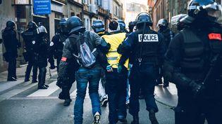 """Une manifestante """"gilet jaune"""" arrêtée par la police lors d'une manifestation à Toulouse, le 9 février 2019. (VALENTIN BELLEVILLE / HANS LUCAS / AFP)"""