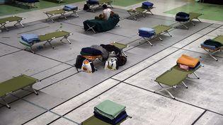 Des lits de camp sont installés dans un gymnase, le 28 décembre 2014, à Paris (Ile-de-France). (DOMINIQUE FAGET / AFP)