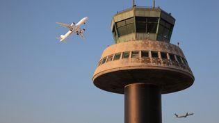 Un avion passe devant la tour de contrôle de l'aéroport de Barcelone (Espagne). (MANUEL COHEN / AFP)