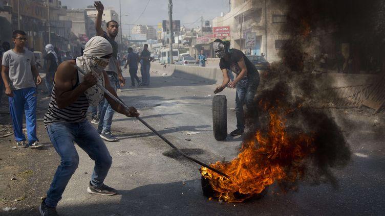 Des Palestiniens brûlent des pneus face aux troupes israéliennes au checkpoint de Qalandia entre Jérusalem et la ville cisjordanienne de Ramallah, le 6 octobre 2015. (MAJDI MOHAMMED / AP / SIPA )