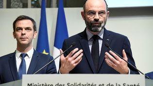 Le ministre de la Santé Olivier Véran, derrière le Premier ministre Edouard Philippe, le 6 mars 2020, lors d'une conférence de presse, à Paris. (BERTRAND GUAY / AFP)