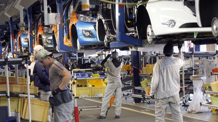 Des ouvriers de PSA assemblent des Peugeot 207 et 208 dans l'usine de Poissy (Yvelines), le 27 janvier 2012. (THOMAS SAMSON / AFP)