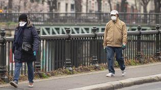 Deux personnes munies de masques marchent dans la rue, à Paris, le 20 mars 2020. (HUGO PASSARELLO LUNA / HANS LUCAS / AFP)