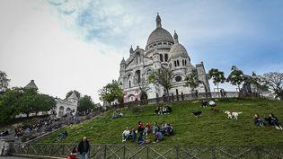 Des gens sont assis sur la pelouse devant la basilique du Sacré-Cœur à Paris, le 12 mai 2020 (photo d'illustration). (BERTRAND GUAY / AFP)