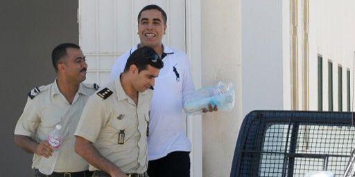 Le rappeur Klay BBJ (Ahmed Ben Ahmed) est escorté par des policiers à sa sortie du tribunal de Hammanet (60 km au sud de Tunis), le 26 septembre 2013. (AFP - Fethi Belaid)
