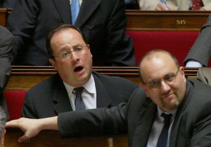 Le premier secrétaire du Parti socialiste François Hollande intervient lors de la séance de questions au gouvernement, au côté du porte-parole du PS Julien Dray, le 23 juin 2004 (PIERRE ANDRIEU / AFP)