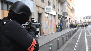"""Un policier tient un LBD, à Bordeaux le 2 mars 2019, lors d'une manifestation de """"gilets jaunes"""". (MEHDI FEDOUACH / AFP)"""
