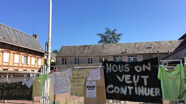 Des banderolles des salariés sont accrochées sur la grille d'entrée de la papeterie Arjowiggins à Bessé-en-Braye. (GREGOIRE LECALOT / RADIO FRANCE)