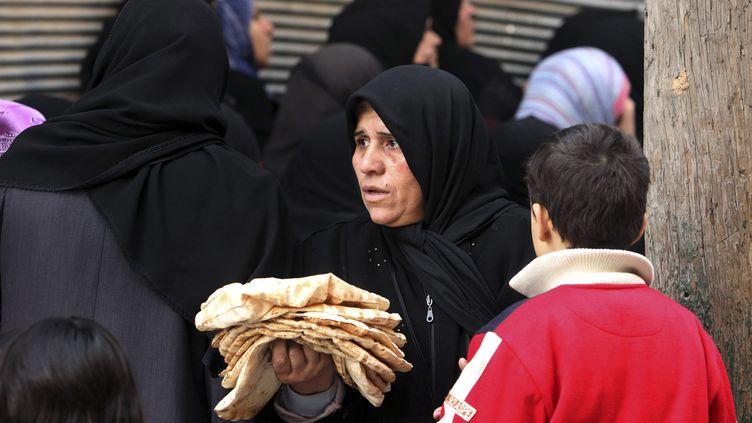 """Une femme porte des pains """"pita"""" à Damas (Syrie), le 25 décembre 2012. (MUZAFFAR SALMAN / REUTERS)"""