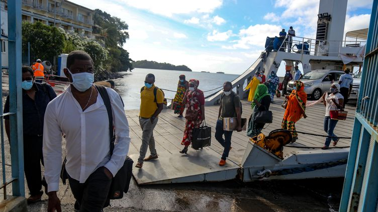 Des passagers descendent de bateau àMamoudzou, sur l'île de Mayotte, en juin 2020 (illustration). (ALI AL-DAHER / AFP)
