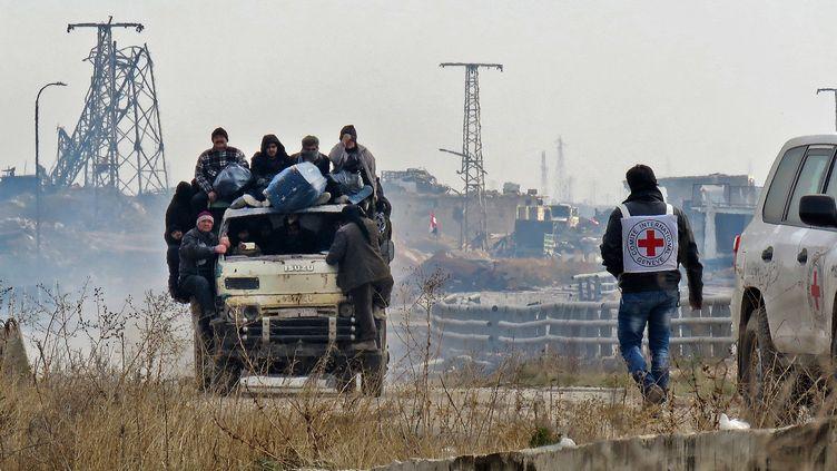 Des habitants sont évacués des quartiers rebelles d'Alep (Syrie), le 16 décembre 2016, sous le regard d'un membre du Comité international de la Croix-Rouge. (AFP)