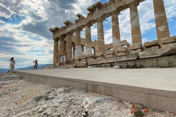 Des touristes prennent des photos devant le temple antique du Parthénon, sur la colline de l'Acropole, après des travaux de réaménagement du site, à Athènes, le 4 juin 2021 (ARIS MESSINIS / AFP)