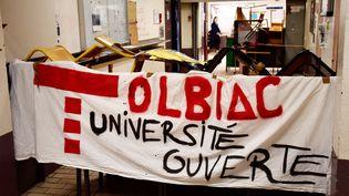 Une banderole est accrochée sur une barricade, dans un couloir de faculté parisienne de Tolbiac, le 4 avril 2018. (CHRISTOPHE SIMON / AFP)