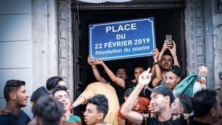 """Des manifestants sous le porche d'un immeuble brandissent une pancarte """"Place du 22 février 2019"""" à Alger, le 14 juin 2019. (SABRI BENALYCHERIF / HANS LUCAS)"""