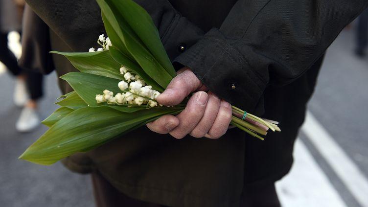 Un manifestant tient un brin de bouquet, le 1er mai 2016, à Toulouse (Haute-Garonne). (REMY GABALDA / AFP)