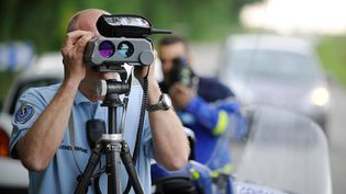 Un gendarme contrôle la vitesse de véhicules avec un radar, le 1er juin 2014, près de Nantes (Loire-Atlantique). (JEAN-SEBASTIEN EVRARD / AFP)