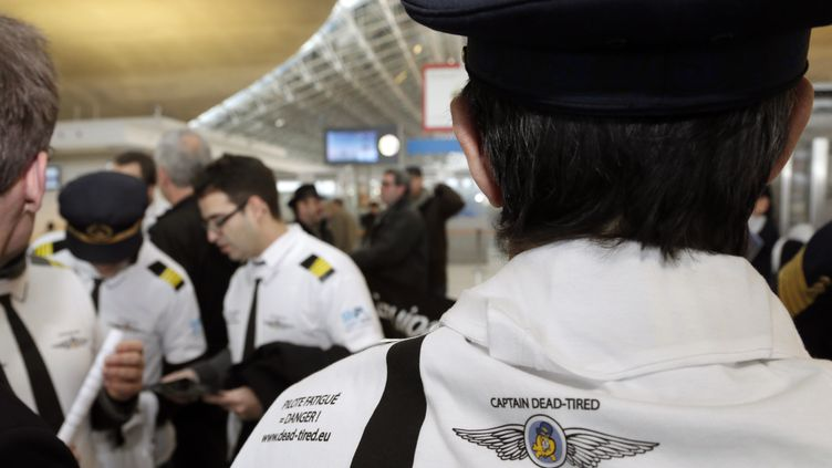 """Un pilote porte un t-shirt avec l'inscription """"commandant de bord épuisé"""", lors d'une manifestation de personnels navigants, à l'aéroport deRoissy, près de Paris, le 22 janvier 2013. (JACQUES DEMARTHON / AFP)"""